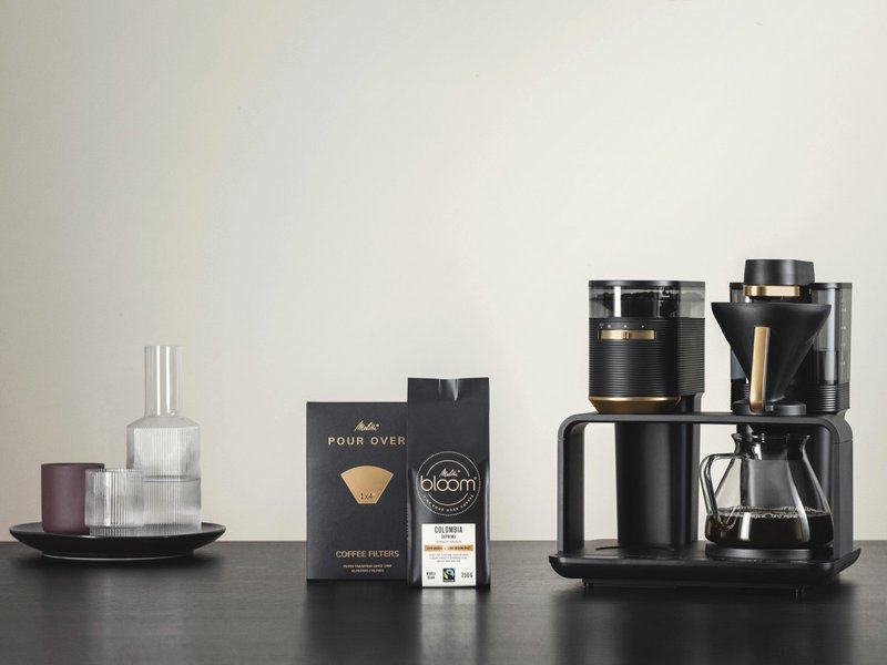 Melitta® EPOS® in an elegant design in black and gold, with the matching Melitta® BLOOM® coffee and Melitta® Pour Over 1X4® filter